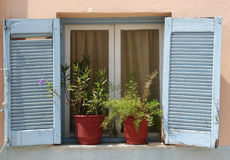 Beautiful Greek blue wooden box with shutters and curtains in the old house Royalty Free Stock Photos