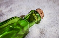 A beautiful green bottle in the sand Stock Photos