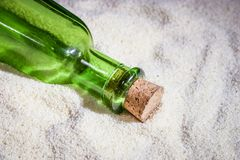 A beautiful green bottle in the sand Royalty Free Stock Photo