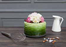 Beautiful green cake decorated with flowers stands on dark wooden board, near corolla and white pitcher Royalty Free Stock Photos
