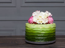 Beautiful green cake decorated with flowers stands on dark wooden board Stock Photo