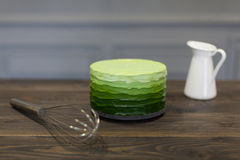 Beautiful green cake stands on dark wooden board, close corolla and white pitcher Royalty Free Stock Photography