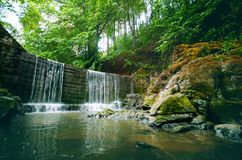 Beautiful green countryside. Waterfall on a river with big rocks and deciduous forest. Green landscape. Beautiful green countryside. Waterfall on a river with Stock Photo