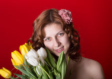 Beautiful green-eyed girl with a bouquet of tulips Royalty Free Stock Photos