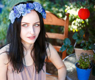Beautiful green eyed girl in wreath with blue flowers. Beautiful black-haired and green eyed girl in wreath with blue flowers sitting in the colourful summer royalty free stock images