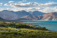 Beautiful green field. View at Pangong lake with some tents for tourist and mountain range background Stock Photos