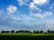 Beautiful green flat landscape with deep blue sky and clouds. In the Belgian Kempen, province Antwerpen, Turnhout stock images