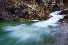 In the beautiful green forest on the huge rocks the fast tempestuous mountain waterfall flows. Stock Photography
