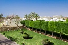 Beautiful garden at hotel resort and building in traditional arabic style. Beautiful green garden at hotel resort and building in traditional arabic style Stock Photography