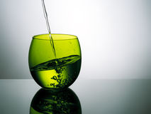 Beautiful green glass of water, pouring, splashing. Stock Photo