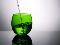 Beautiful green glass of water, pouring, splashing. Royalty Free Stock Images
