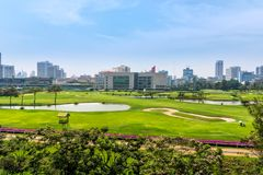 Golf course in hart of Bangkok, city skyline in the background. Beautiful green golf course in hart of Bangkok, city skyline in the background, Thailand royalty free stock photography