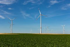 Wind turbines in a agriculture landscape. Beautiful green hill with white wind turbines with red stripes generating electricity on a bright blue cloudy sky in royalty free stock photography