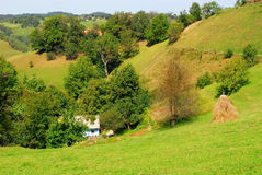 Beautiful green hills and small house at the countryside Royalty Free Stock Images