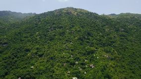 Beautiful green mountain covered tropical trees and stones aerial view. Landscape mountain with green forest drone view. Beautiful green mountain covered stock video