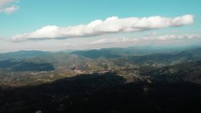Beautiful green mountain highs against blue sky with clouds. Drone flying along mountain valley.  Drone flight above mountain vill. Age. Ukrainian villages in stock video
