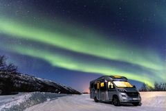 Beautiful green northern lights and camper with light inside. Travel in Norway royalty free stock photography