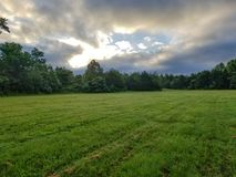 Open field with open sky. Beautiful green open field with grass cutting on it surrounded by trees, open cloudy sky with silver lining and a hole int he middle stock photography