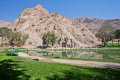 Beautiful green park with lake, montains and historical site - Arches of Taq-e Bostan, Iran. Stock Photography