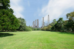 Beautiful green park with oil refinery and smokestack in backgro Royalty Free Stock Photography