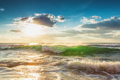 Beautiful green sunrise wave. Ocean waves and beautiful sunrise over the beach Royalty Free Stock Photography