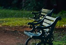 Sitting chairs in a park stock. The beautiful green traditional sitting chairs captured from a botanical garden in Bangalore, India Stock Photo