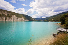 Beautiful green water of Lake Castillon reflects the sky and woo Royalty Free Stock Images
