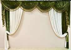 Beautiful green white velvet curtain on beige wall. Beautiful green white velvet curtain on a beige wall Royalty Free Stock Photo