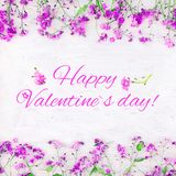 Beautiful greeting card Happy Valentine`s Day. Beautiful greeting card Happy Valentines Day. Floral arrangement of small pink flowers lying on white grunge wood Stock Photo