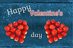 Beautiful greeting card with Valentines Day - hearts made from strawberries on the background of grunge wooden texture and the royalty free stock photography