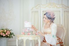 Beautiful greyhead woman in Rococo dress posing in front of historic background while decorating a cake stock image