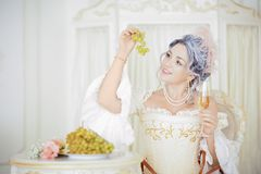 Beautiful greyhead woman in Rococo dress posing in front of historic background while eating grapes royalty free stock images