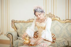 Beautiful greyhead woman in Rococo dress posing in front of pink background while pouring tea from the kettle royalty free stock photo