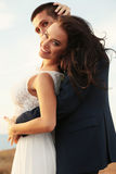 Beautiful groom and bride in wedding clothes posing on sea coast Royalty Free Stock Photos