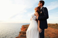 Beautiful groom and bride in wedding clothes posing on sea coast Royalty Free Stock Images