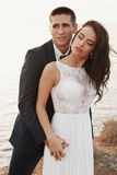Beautiful groom and bride in wedding clothes posing on sea coast Royalty Free Stock Photography