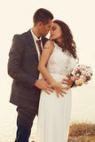 Beautiful groom and bride in wedding clothes posing on sea coast Stock Images