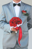 Beautiful groom with red wedding bouquet flowers Stock Image