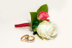 Beautiful groom`s boutonniere of white and red roses and wedding rings on a white table.  Royalty Free Stock Image