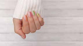 Beautiful groomed woman`s hands with colored nails on the wooden background. Manicure, pedicure beauty salon concept. Empty place. For text or logo stock images