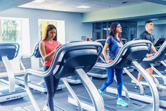 Beautiful Group Of Young Friends Exercising On A Treadmill Royalty Free Stock Photo