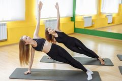 Beautiful group of women practicing the side plank yoga pose during a class in a gym.  royalty free stock photography
