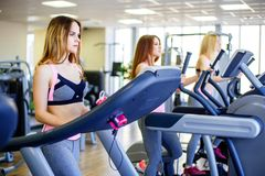Beautiful group of young women friends exercising on a treadmill at the bright modern gym. Beautiful group of young women friends exercising on a treadmill at royalty free stock photography