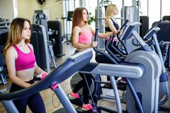 Beautiful group of young women friends exercising on a treadmill at the bright modern gym. Beautiful group of young women friends exercising on a treadmill at stock photo