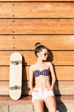 Beautiful gsexy girl with skateboard poses against wooden wall Royalty Free Stock Photo