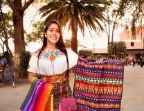 Beautiful guatamalian girl salling traditional colorful fabric. ANTIGUA, GUATEMALA-DEC 26, 2015: : Beautiful guatamalian girl salling traditional colorful fabric royalty free stock images