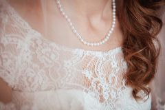 Beautiful guipure on a dress of the bride. Pearl necklace on Stock Photography