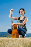 Beautiful guitarist posing outdoors Stock Image