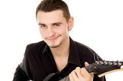 Beautiful guy dressed in black clothes sits and plays the guitar Royalty Free Stock Photography