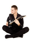 Beautiful guy dressed in black clothes sits and plays the guitar Royalty Free Stock Images